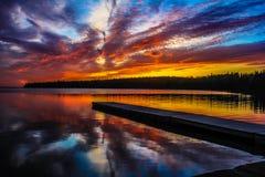 Embarcadero que sigue la puesta del sol en el lago claro Fotografía de archivo