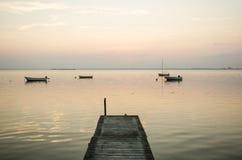 Embarcadero viejo con los barcos de rowing anclados en el agua Imagen de archivo