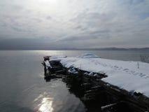 Embarcadero viejo cubierto con nieve en el golfo del Océano Pacífico fotos de archivo