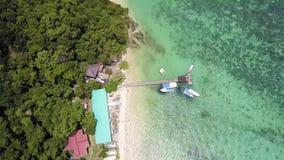 Embarcadero y barco de la visión aérea en la isla de Manukan de Borneo almacen de metraje de vídeo