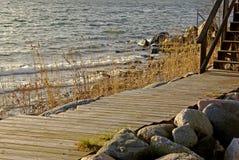 Embarcadero y escalera de madera por la orilla del agua en invierno Fotografía de archivo libre de regalías