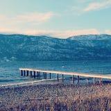 Embarcadero y montañas del lago en día de invierno ventoso Imagenes de archivo