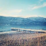 Embarcadero y montañas del lago en día de invierno ventoso Fotos de archivo