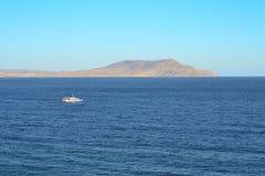 Embarcation de plaisance flottant sur un fond des montagnes et d'un ciel sans nuages Photos libres de droits