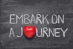 Embark on journey heart. Embark on a journey phrase handwritten on chalkboard with red heart symbol instead of O stock photography