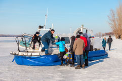 Embarkation people on the passenger hovercraft at the ice of the Royalty Free Stock Photography