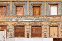 Embarqué vers le haut de la peinture abandonnée d'écaillement de façade de construction Images libres de droits