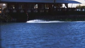 Embarque da vigília do treinamento do desportista na superfície da água do complexo moderno do esqui aquático video estoque
