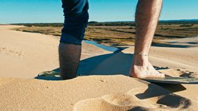 embarque de la arena del hombre joven en las dunas de arena del desierto cerca de la ciudad foto de archivo