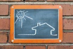 Embarque em uma parede de tijolo com uma casa e um sol Imagem de Stock