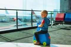 Embarque que espera del niño para al vuelo en pasillo del tránsito del aeropuerto foto de archivo