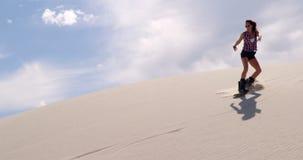 Embarquement de sable de femme sur la pente dans le désert 4k banque de vidéos