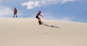 Embarquement de sable de femme tandis qu'homme observant son 4k banque de vidéos