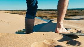 embarquement de sable de jeune homme aux dunes de sable de désert près de la ville photo stock
