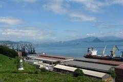 Embarquez décharger des grues un jour d'été dans la baie du port Extrême Orient photos stock