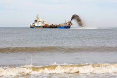 Embarquez le sable de pompage sur la plage pour la défense côtière Image stock