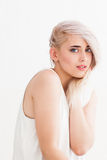 Embarrassed blonde with beautiful blue eyes Stock Images