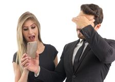 Embarrassed Boyfriend Shows The Cell Phone Screen To His Girlfriend. Couple Sharing Gossip.. Royalty Free Stock Photo