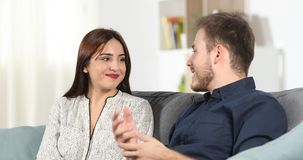 Embarrassed girl talking hiding smile. Embarrassed girl talking with a man during a date hiding smile with her hand at home stock footage