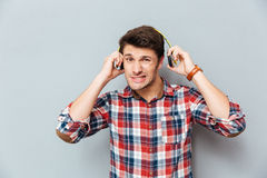Embarrassed �irritated young man in checkered shirt taking off headphones. Over grey background Royalty Free Stock Photos