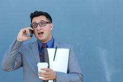 Embarrassed-looking businessman listening to someone on cellphone - Stock image Stock Image