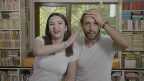 Embarrassed millennial man slapping his forehead doing facepalm next his girlfriend happy funny couple having fun -. Embarrassed millennial man slapping his stock video