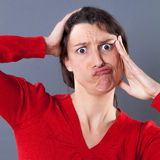 Embarrassed pouting young woman making a grimace for regret Stock Photos
