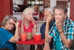 Embarrassed Seniors with Loud Friend. Loud mouth women embarrassing group of friends in cafe Royalty Free Stock Photography