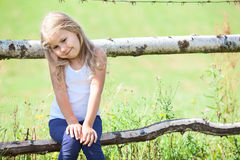 Embarrassed small girl sitting on rural fence Royalty Free Stock Image