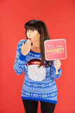Embarrassed woman in blue sweater holding naughty sign Royalty Free Stock Photos