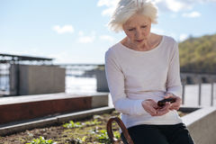 Embarrassed woman having high fever in the park. Viruses around us. Beautiful upset senior pensioner sitting and recalculating pills in the street while feeling Royalty Free Stock Photography
