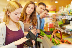 Embarrassed woman looking for money at checkout Royalty Free Stock Photography