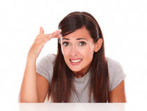 Embarrassed young woman with fail gesture. Front view portrait of embarrassed young woman with fail gesture looking at camera on isolated studio stock photography