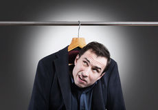 Embarrassing situation concept. Man in suit hanging in the wardrobe Royalty Free Stock Photography