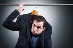 Embarrassing situation concept. Man in suit hanging in the wardrobe Stock Photo