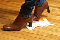 Embarrassing. A woman unknowingly tracks a piece of toilet paper on the bottom of her boot which makes for an embarrassing time Royalty Free Stock Photos