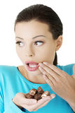Embarrassment woman with chocolates Stock Photo
