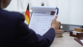 Embassy employee approving visa application, German flag on table, authority. Stock footage stock video