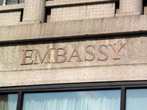 Embassy Sign. Gold Embassy Sign on pink granite Stock Photography