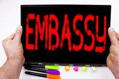 Embassy text written on tablet, computer in the office with marker, pen, stationery. Business concept for Tourist Visa Application. White background with space Royalty Free Stock Image