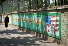 Embassy of the United States, Tehran. Cladded Iranian woman in front of Embassy of the United States, Tehran with walls painted with propaganda statements royalty free stock photo