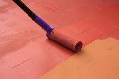 Embauchez le peintre peignant un plancher sur le rouge de couleur Image libre de droits