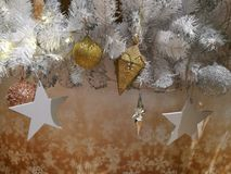 Embellished Christmas tree decoration gold ornament, hanging ball, silver star and tinsel Royalty Free Stock Photography