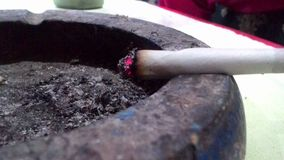 Embers of a cigarette over an ashtray Royalty Free Stock Image