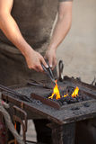 Embers, fire, smoke, tools and hands of blacksmith Stock Photo