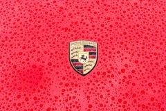 Emblème de capot de voiture de sport Porsche en gouttes de pluie sur le fond rouge Photos stock