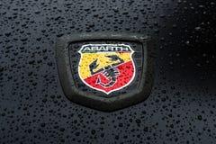 Emblem av en bil Abarth i regndroppar Arkivfoton