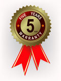 Emblem of golden color with red ribbons and text for five years of warranty Royalty Free Stock Image