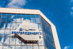 Emblem and logos on glass mirror facade of building Belgorodenergo on a blue cloudy background. Belgorod, Russia. Stock Image