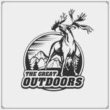 Emblem med berg och härliga hjortar vektor illustrationer